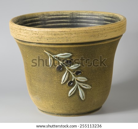 Rustic ceramic flowerpot in ocher with stylized decorative olives ornaments - stock photo