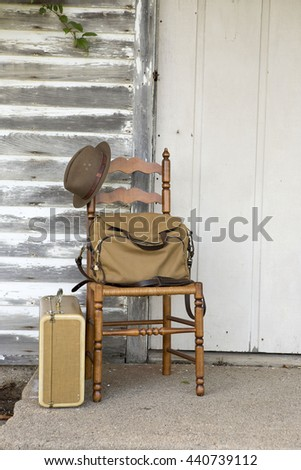 Rustic chair with travel bags in front of old one room school house.