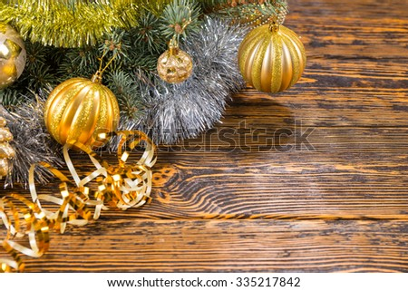 Rustic Christmas bauble background with golden balls on a fir branch over a rustic wood background with gold tinsel and copyspace for your Xmas greeting - stock photo