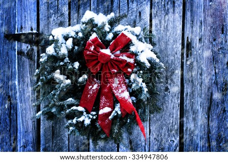 Rustic Christmas wreath on old weathered barn in a snow storm.