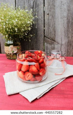 Rustic composition with glass top full of sweet tasty ripe strawberry and bouquet of cute wildflowers in a vase decorated with jute and wooden ladybirds. Vintage decor foe dessert. Romantic style - stock photo