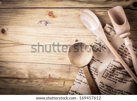Rustic cooking utensils with a wooden spoon, ladle and scoop lying on a folded cloth with a recipe on it on an old cracked wooden table with vignetting and copyspace - stock photo