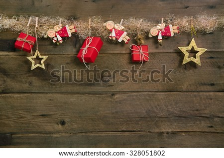Rustic country style christmas background with red gift boxes and hanging angels. - stock photo