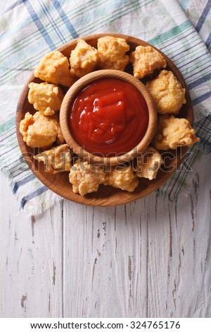 rustic crispy popcorn chicken fillet with sauce on a plate vertical top view - stock photo
