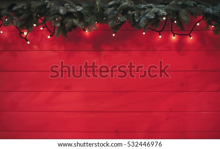 Rustic decorative Christmas,New Year tree branch,garland light on red wooden background.Copy space to place text letters.Bright holiday banner backdrop.Vibrant wood back ground.Copyspace on bottom