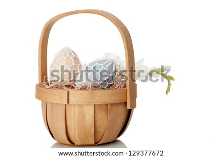 Rustic Easter Egg gift in a quaint little cane basket with a fresh white spring flower on a white studio background