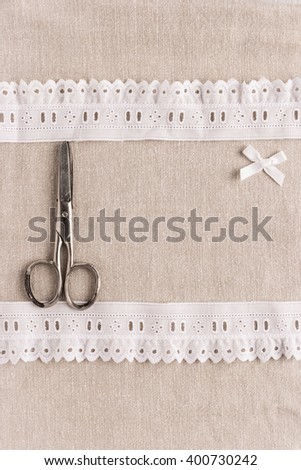 Rustic fabric for sewing, lace, scissors and accessories for needlework on old wooden background. Top view with copy space. - stock photo