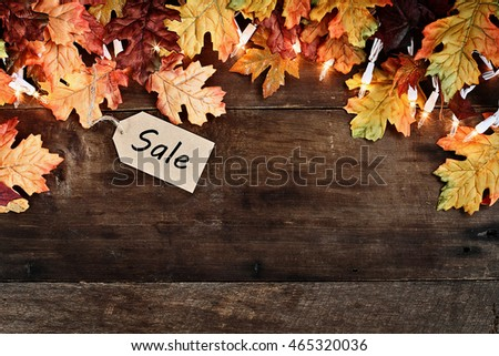 Rustic fall background of autumn leaves and decorative lights with sales tag over a rustic background of barn wood. Image shot from overhead.