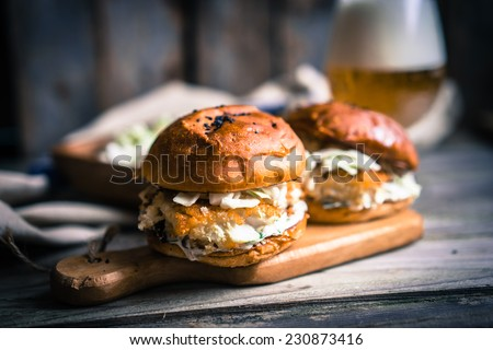 Rustic fish burgers with coleslaw and beer - stock photo