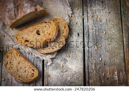 rustic food background with fresh homemade whole wheat bread, top view - stock photo