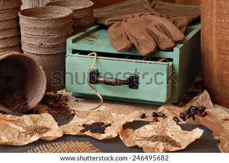 Rustic gardening still life with assorted seeds, organic starter pots, work gloves and vintage wooden box.  Selective focus on drawer with twine. - stock photo