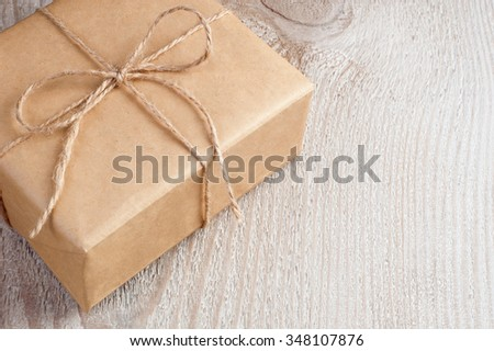 Rustic gift box on rough wooden table painted white with space for text. Gift box packed recycled brown paper and twine. Concepts are holiday gift, eco friendly packing, rustic style gift wrapping. - stock photo