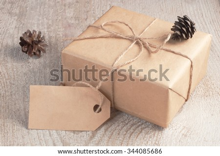 Rustic gift box packed brown paper and twine with blank tag decorated fir cones on old white wooden table - stock photo