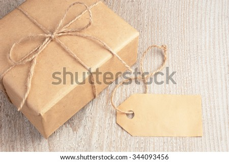 Rustic gift box packed into brown paper tied by twine and blank tag nearby on old white wooden table with space for text - stock photo