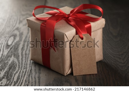 rustic gift box with red ribbon bow and empty tag, on old wood table - stock photo