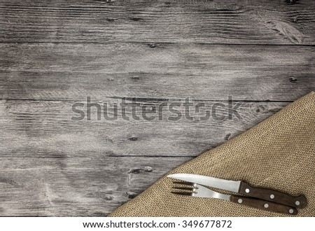 Rustic grange wood table top background with linen napkin, knife and fork. Can be used for restaurante or bar  menu list. Menu background template. Steak house menu design. Cutlery set on wood table.