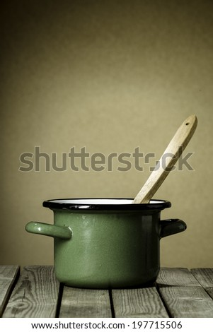 Rustic green enameled cooking pot with a wooden ladle inside standing on a wooden kitchen table against a brown wall with copyspace - stock photo