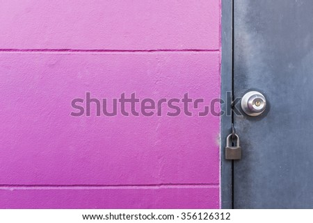 rustic grey metal door with knob and lock on texture groove pink wall - stock photo