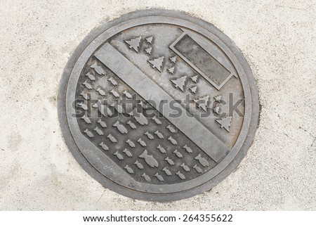 Rustic grunge storm drain manhole cover on  street - stock photo
