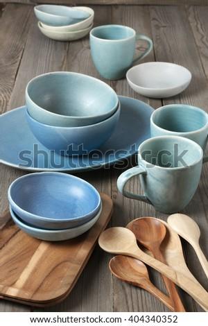 Rustic handmade blue ceramic dishware, wood tray and spoons on wooden table.