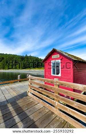 Rustic harbor dock with a wooden hut painted red. Location: San Juan Islands, Washington State. Copy space  - stock photo