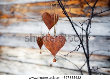 Rustic hearts hanging against weathered wood
