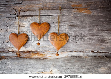 Rustic hearts hanging against weathered wood - stock photo