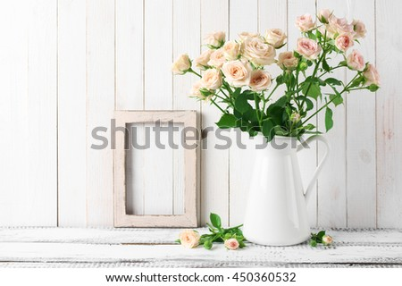 Rustic home decoration: light pink roses bouquet in jug and photo frame against white rustic wooden wall. - stock photo