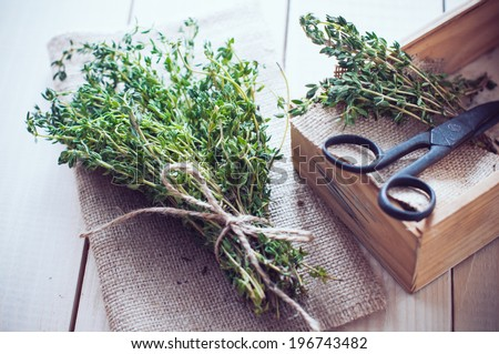 Rustic home kitchen still life, dried herbs, old boxes and vintage scissors on a wooden table. - stock photo