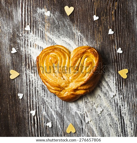 Rustic homemade heart shape bun on wooden background - stock photo