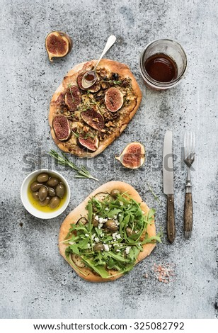 Rustic homemade pizzas with eggplant, cheese, olives, arugula, prosciutto and figs over grunge backdrop. Top view - stock photo
