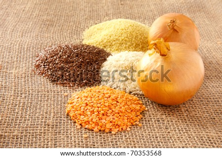 Rustic image of piles of grain with two onions - stock photo