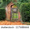 Rustic ivy covered arched gateway and red brick wall into an English garden - stock photo