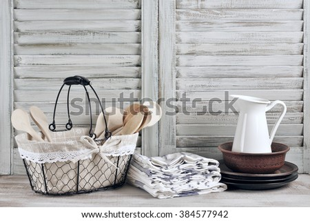 Rustic kitchen still life: wire basket with wooden spoons, jug, ceramic dishware and towels stack against vintage wooden shutters.