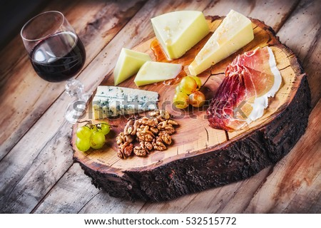 Rustic mediterranean cheese board and a glass of red wine