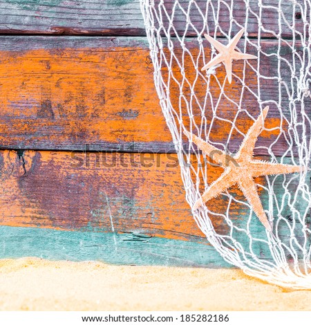Rustic nautical background with starfish hanging in a fishing net against weathered painted wooden boards in blue and orange with copyspace over golden tropical beach sand - stock photo