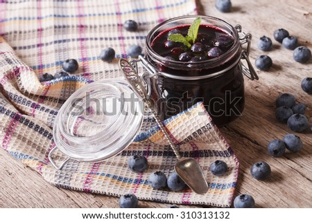 Rustic of blueberry jam in a glass jar close up on the table. Horizontal - stock photo
