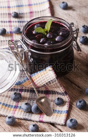 Rustic of blueberry jam in a glass jar close up on the table. vertical - stock photo