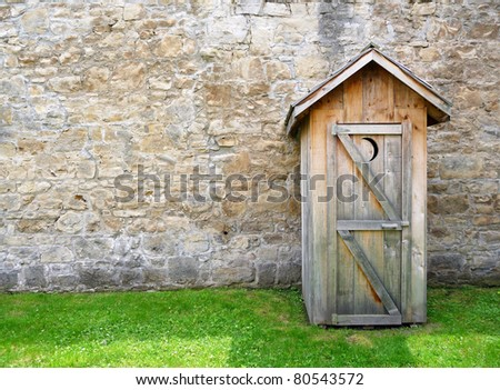 Rustic outhouse and vintage stone wall - stock photo