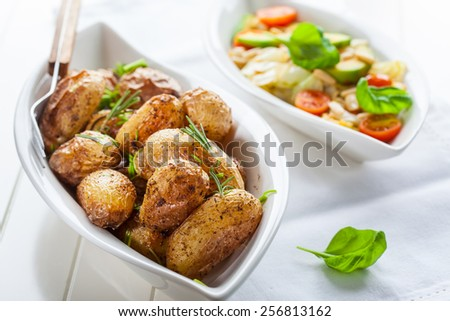 Rustic oven baked potatoes with cabbage salad - stock photo