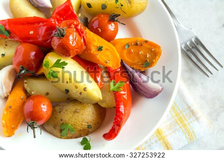 Rustic oven baked vegetables with spices and herbs on white plate close up, vegetarian organic autumn meal