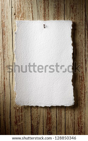 rustic paper sheet on aged wooden wall - stock photo