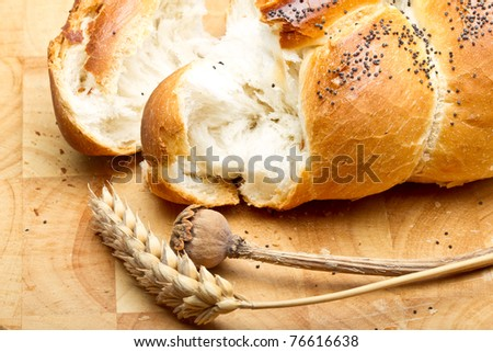 Rustic poppy seeded bread with dried cereal ear and poppy stem. - stock photo