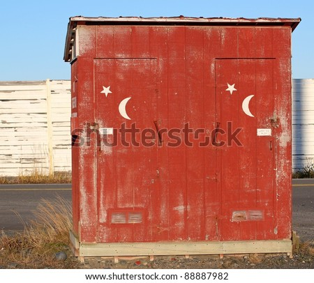Rustic public restroom building with moon and stars painted on the doors.