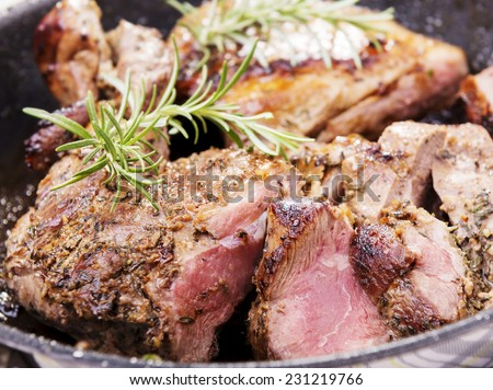 Rustic roast lamb with pan juices and rosemary - stock photo