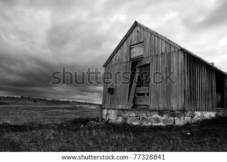 Rustic Ruins Of An Old Abandoned Wooden Shed Decay In A Tasmanian (Australia) Farm Field, While Fierce Rain Clouds Form In The Skies Above - stock photo