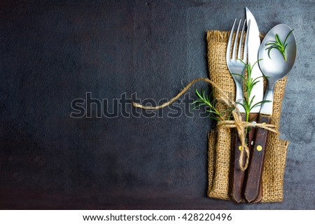 Rustic set of cutlery knife, spoon, fork. Black background. Top view - stock photo