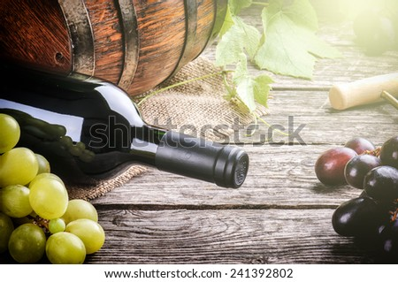 Rustic setting with bottle of red wine and fresh grape  - stock photo
