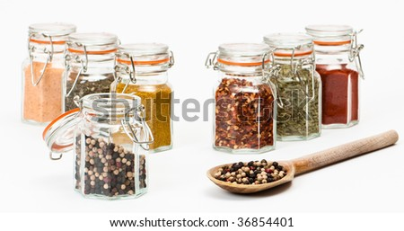 Rustic spoon full of peppercorns with spice jars on white background - stock photo