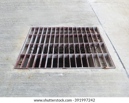 rustic square manhole drain cover in the street - stock photo